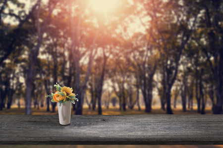 Artificial flower on Old Wooden plank and blurry forest in background. Stock Photo