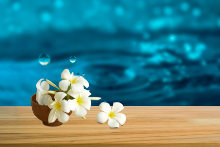 Beautiful White flowers (Plumeria) with waterdrop on wooden table.