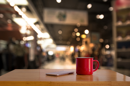 A red cup on wooden table and blurry light in background.