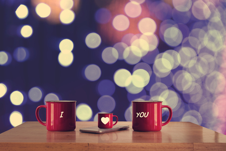 Three red cup on wooden table and blurry light in background.  Love and Family concept. Stock Photo
