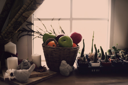 Artificial Fruits in a basket on wood table. Home decoration. Light and Shadow. Stock Photo