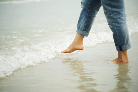 Woman playing with the water on beach by using foot. Travel concept.