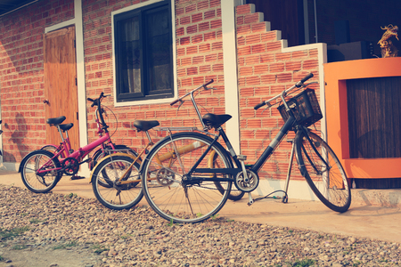 Four Old Bicycle parking by the brick wall. Stock Photo