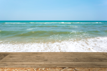 Empty wooden table for display product and Blurry sea in background. Stock Photo