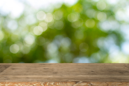 Empty wooden table for display product and Blurry green nature background.