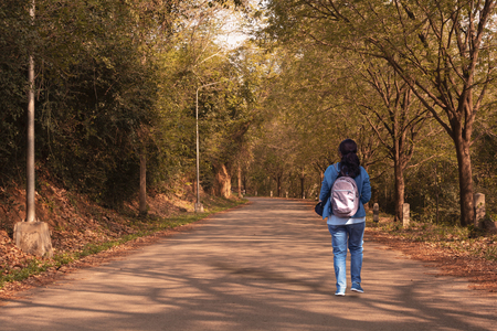 Kaeng Krachan National Park, Phetchaburi, Thailand. A woman walking alone on the road among forest. Stock Photo