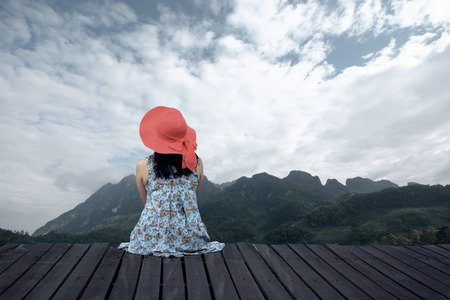 Woman relaxing on wooden terrace and looking beautiful mountain.