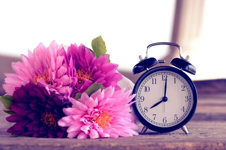Retro alarm clock and flower bouquet on wooden plank
