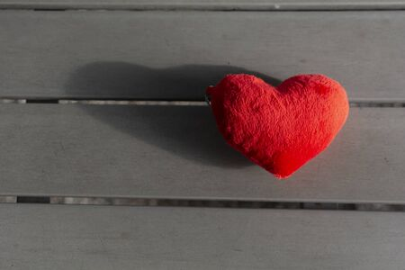The Red Heart placed on wood table. You can put your word or text in the copyspace.