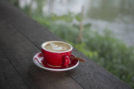 A cup of Latte on wooden table.