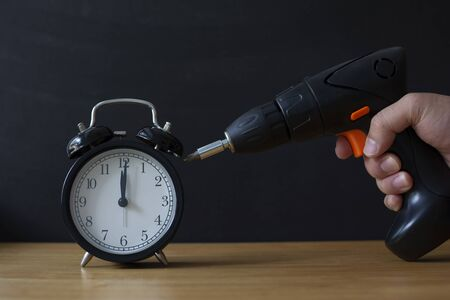 Retro alarm clock and Electric driller.  Time Management Concept.