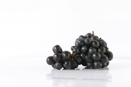 Bunch of Black Seedless Grapes isolated on white background.