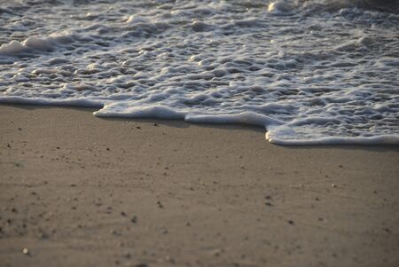 The bubbles of the sea that pass through the waves washing the beach