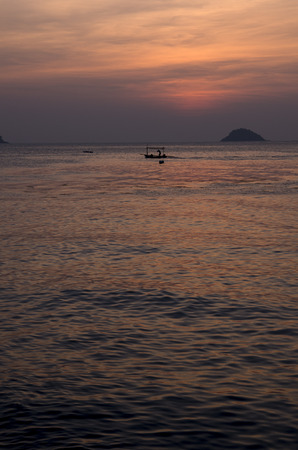 Fishing barge floating on the water in the sunset at the coasts of Koh Chang in Thailand.