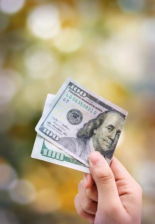 one hundred dollars: Money in hand, isolated on orange background bokeh