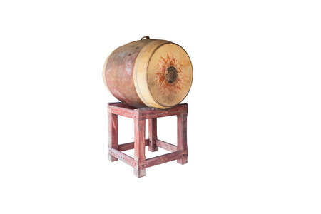thai musical instrument: Yellowish old large drum with drum skin fully visible isolated on white . The drum is used in temple to notify the time for midday meal. The drum skin side is typically as large as half of human height