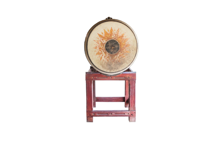 thai musical instrument: Yellowish old large drum with drum skin fully visible isolated on white. The drum is used in temple to notify the time for midday meal. The drum skin side is typically as large as half of human height
