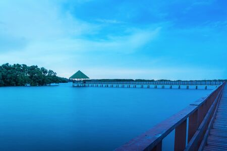 Long exposure, scenery at dusk, wooden bridge in Samut Sakhon Province. Wooden bridge is a tourist attraction in the ecological coastal nature.