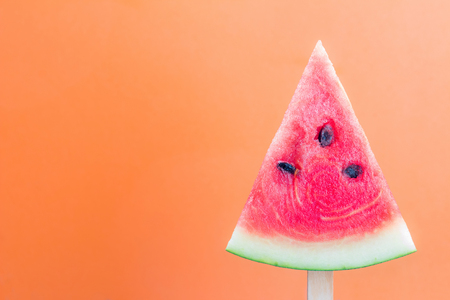 Watermelon sliced into a slice of wood on an orange background.