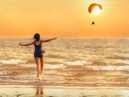 The girl runs into the sea pretending to parody the paramotor flying in the evening, the sun is falling, the concept of relaxation. Zdjęcie Seryjne