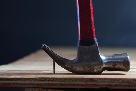 The hammer is levering the nail off the wooden floor. Stock Photo