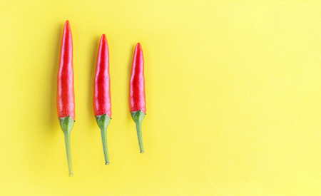 Three red chili peppers arranged on a yellow background. Stock Photo