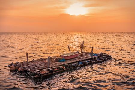 zattera Legno Galleggiante nel mare al tramonto.