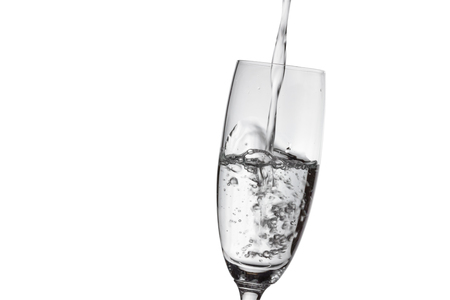 Pouring water into the glass isolated on white background. Banco de Imagens