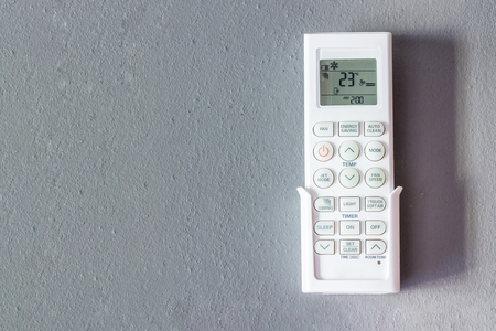 Air Conditioner remote with light switch on room wall.