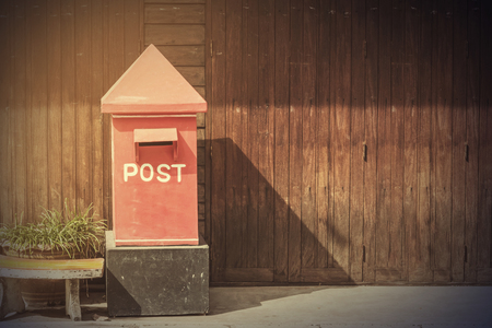 postbox in front of rows of old wooden house,vintage filter. Stock Photo