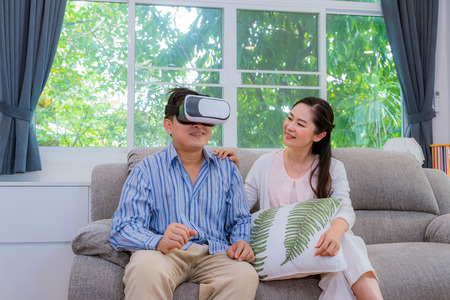 Middle-aged couples, men trying to play VR glasses, women laughing like men, concept Valentines day, happy family concept 版權商用圖片