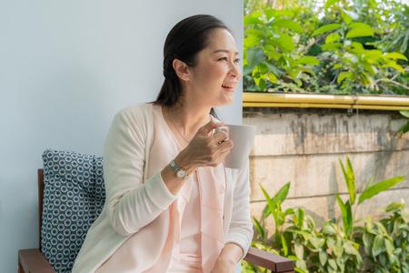 Aziatische vrouwen van middelbare leeftijd zitten koffie te drinken in de achtertuin. Stockfoto