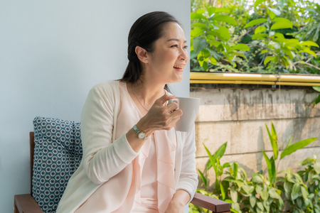 Middle-aged Asian women sit and sip coffee in the backyard. 스톡 콘텐츠