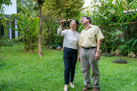 Aziatische bejaarde stellen lopen door de achtertuin om de natuur te zien.