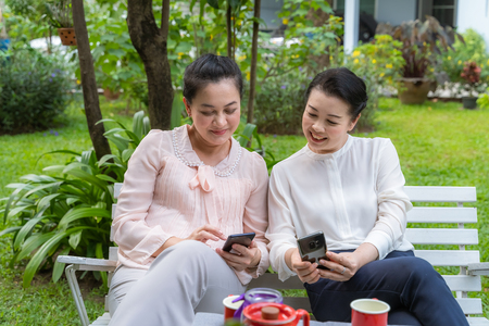 Two Asian middle-aged women who are friends are looking at the phone and talking fun.