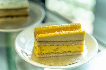 The yellow cake is divided into pieces placed in the dish.