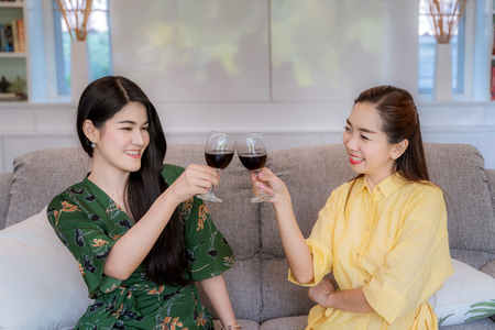Asian women are bumped into a glass of wine to celebrate their success.