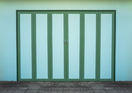 Green wooden doors with green walls, vintage style