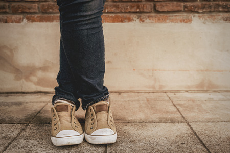 Shapely female cross ones legs  in sneakers and jeans near a concrete wall,vintage style