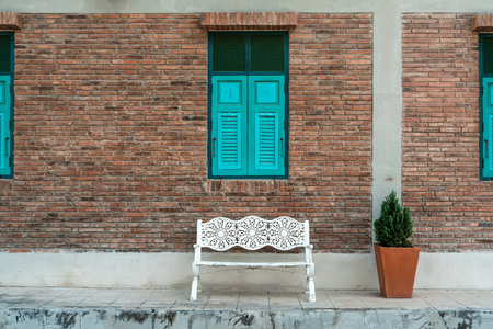 White bench with brick wall with blue window, vintage style 写真素材