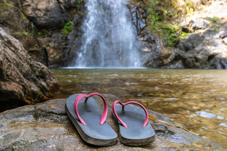 Slippers were placed near the waterfall, carefully thought out of the danger of natural tourism. Standard-Bild