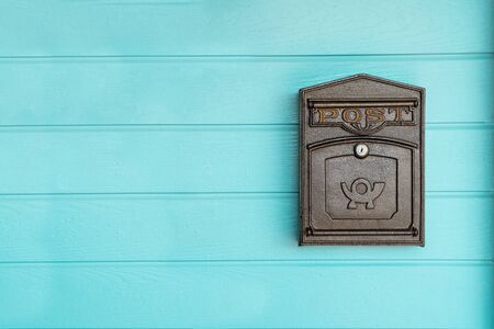 postbox hanging on a blue wood wall Stok Fotoğraf - 132119998