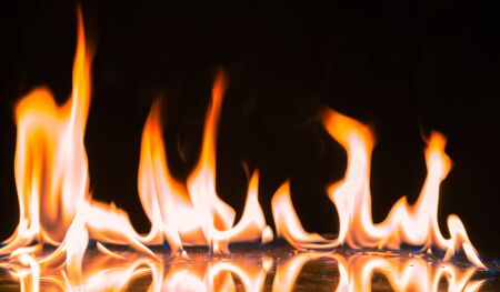 Fire Flames Igniting And Burning.Real fire , A line of real flames ignite on a black background.