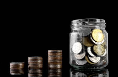 The concept of investment savings, coins stacked and put in jars