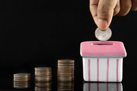 Savings concept for buying a house, Hand putting money coin stack with piggy bank