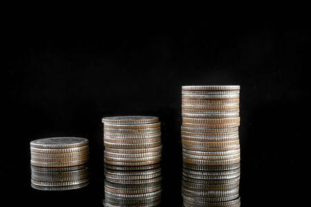 Coins placed stacked on a black background, the concept of investment savings Stok Fotoğraf