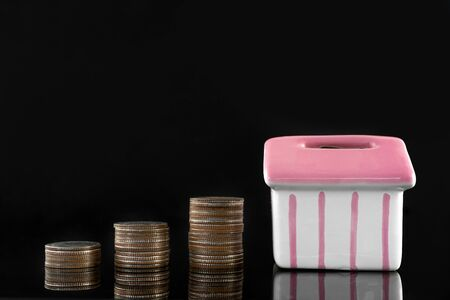 Coins placed stacked and mock up house on a black background, the concept of investment savings