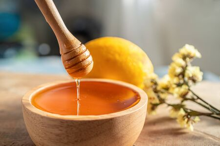 Healthy organic scoop Thick honey dipping with wooden honey spoon from a wooden bowl, honey dripping, pouring honey into the bowl. Close-up. Stok Fotoğraf
