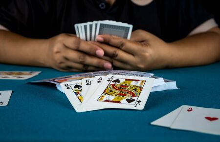 The gambler is playing cards in his hand. Stock Photo