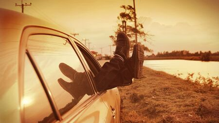 man legs with boots sticking out of a car,During the parking break in driving trip